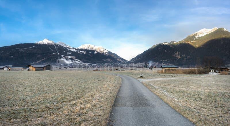 Camino a través del prado congelado y del pueblo austríaco imágenes de archivo libres de regalías