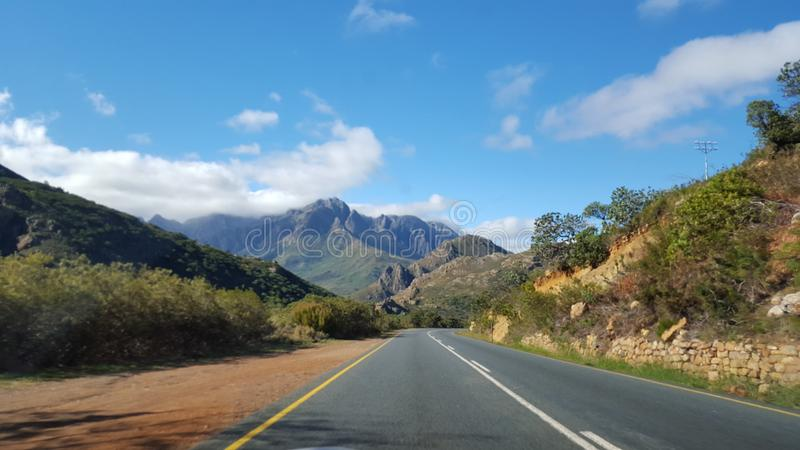 Camino vacío del alquitrán en el Western Cape, Suráfrica con las cordilleras escénicas y la vegetación natural foto de archivo libre de regalías