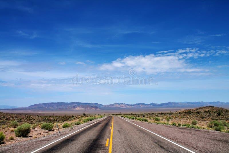 Camino vacío del desierto con el cielo abierto y las montañas distantes en Nevada imagen de archivo