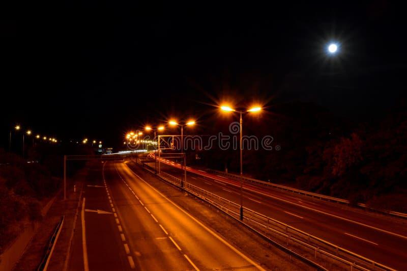 Camino vacío en la noche con las luces anaranjadas imagen de archivo libre de regalías