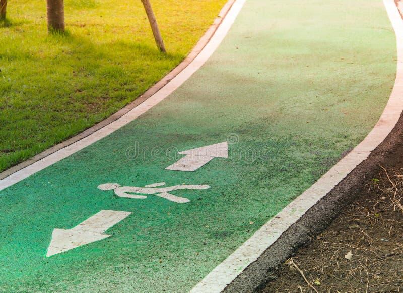 Camino verde para hacer ejercicio o correr y caminar por el jardín del parque público fotografía de archivo