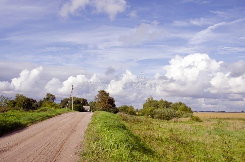 Camino y casa rurales de la grava en distancia imagenes de archivo