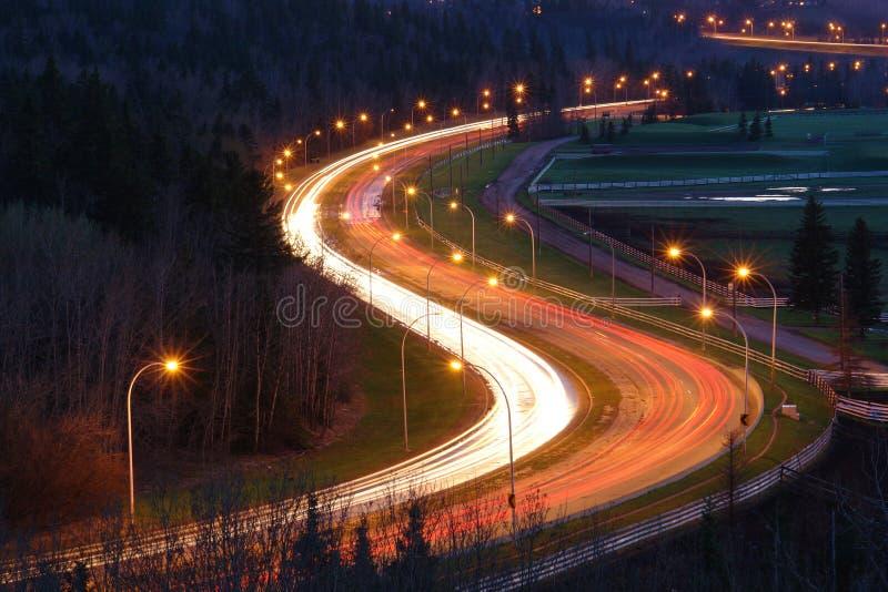 Camino y coches de la dimensión de una variable de S en la noche imagenes de archivo