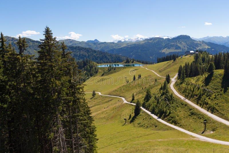 Caminos y un lago azul en las montañas foto de archivo