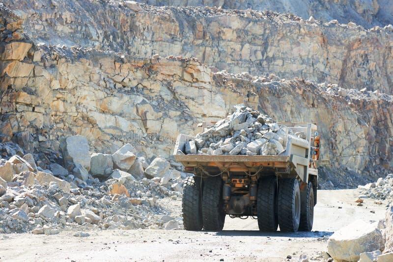 Camion à benne basculante énorme transportant la roche ou le minerai de fer de granit photographie stock