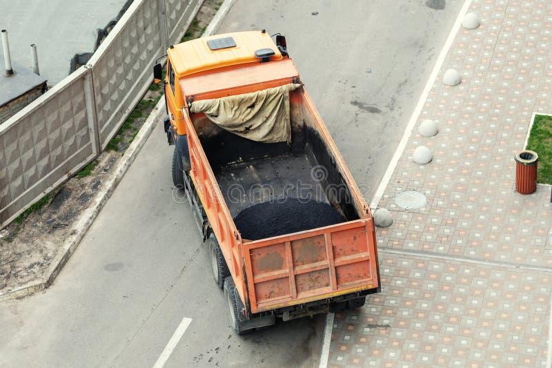 Camion à benne basculante industriel lourd déchargeant l'asphalte chaud Construction de routes de ville et site de renouvellement photo stock