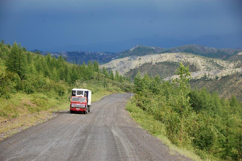 Camion alla strada principale di Kolyma della strada della ghiaia della montagna ad entroterra russa fotografie stock