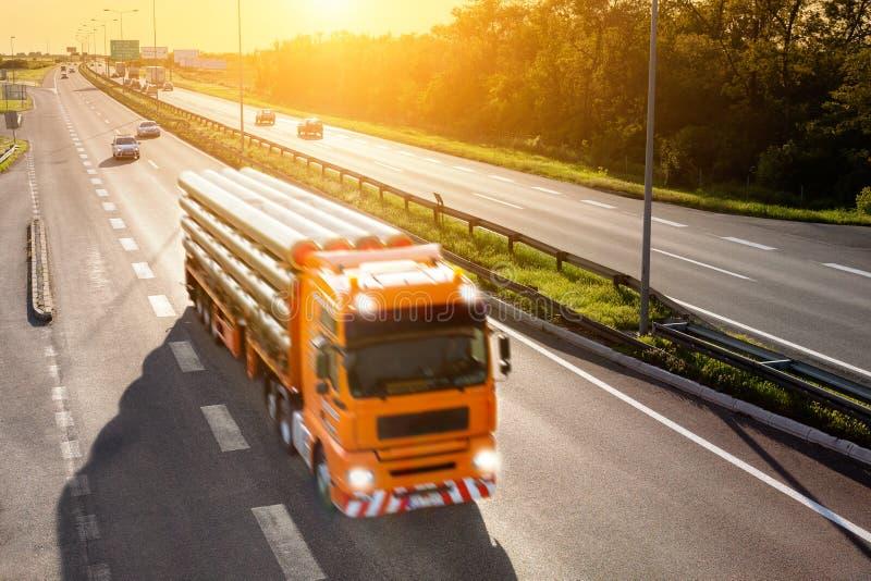 Camion arancio nel mosso sulla strada principale immagine stock libera da diritti