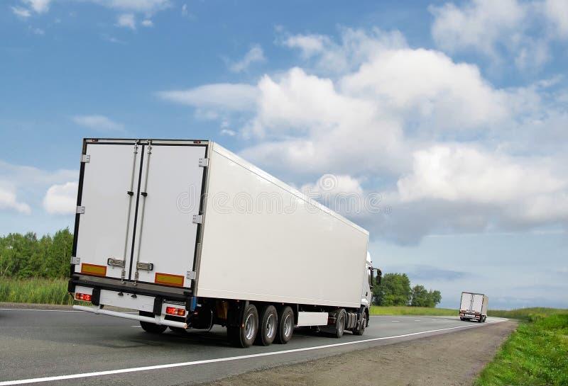 Camion bianchi sulla strada principale del paese sotto cielo blu immagini stock libere da diritti
