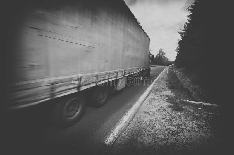 Camion in bianco e nero che accelera sulla strada principale del paese immagine stock