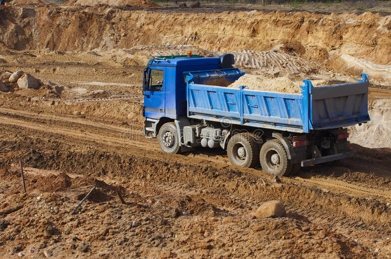 Camion blu e passare attraverso la terra della ghiaia immagini stock libere da diritti