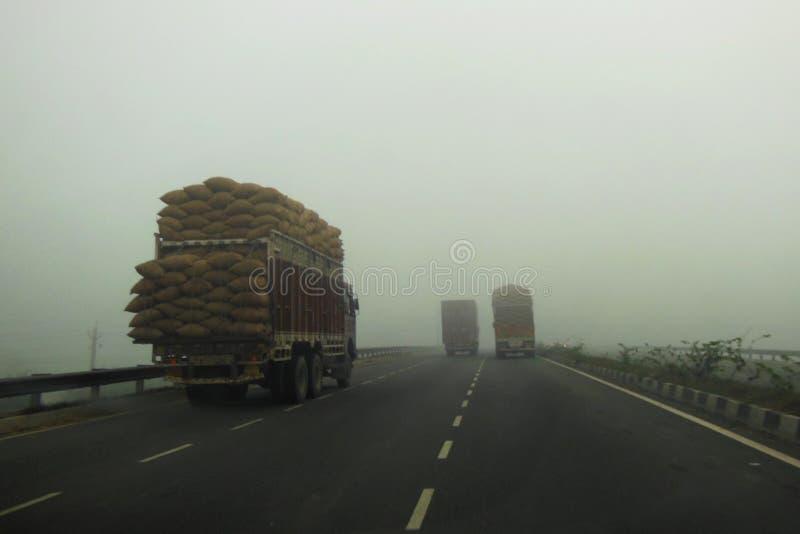 Camion chargé conduisant le zigzag sur la route de Delhi Chandigarh conduisant par le brouillard enfumé brumeux de matin de Delhi image stock