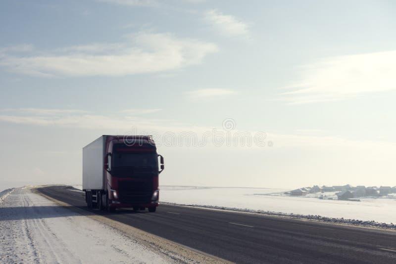 Camion che guida sulla strada asfaltata nel paesaggio rurale di inverno immagine stock libera da diritti