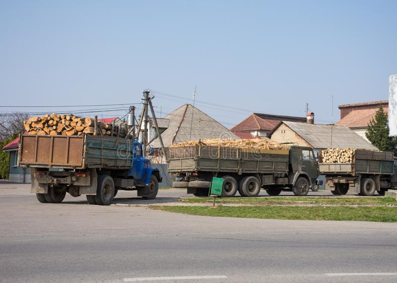 Camion che portano legno su una strada immagine stock