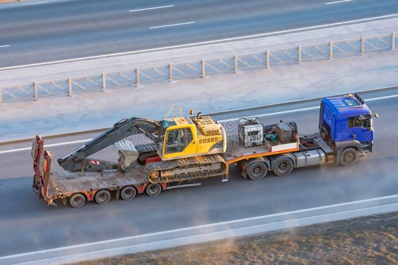 Camion con una piattaforma lunga del rimorchio per il trasporto del macchinario pesante, escavatore caricato del cingolo con il s immagini stock libere da diritti