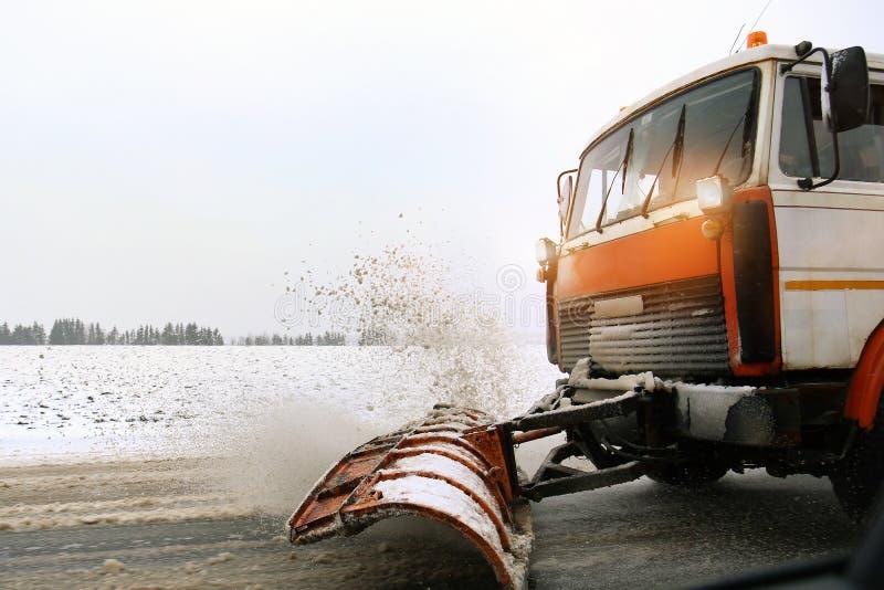 Camion de chasse-neige enlevant la neige sale de la rue ou de la route de ville après les chutes de neige lourdes Situation de ro images stock