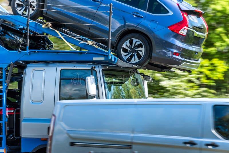Camion del trasportatore caricato con le automobili sull'autostrada britannica nel moto veloce immagine stock libera da diritti