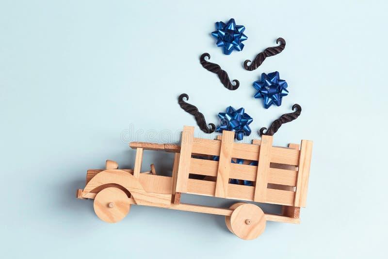 Camion di legno del giocattolo con i baffi ed archi nella parte posteriore su fondo blu Giorno del padre felice immagine stock libera da diritti