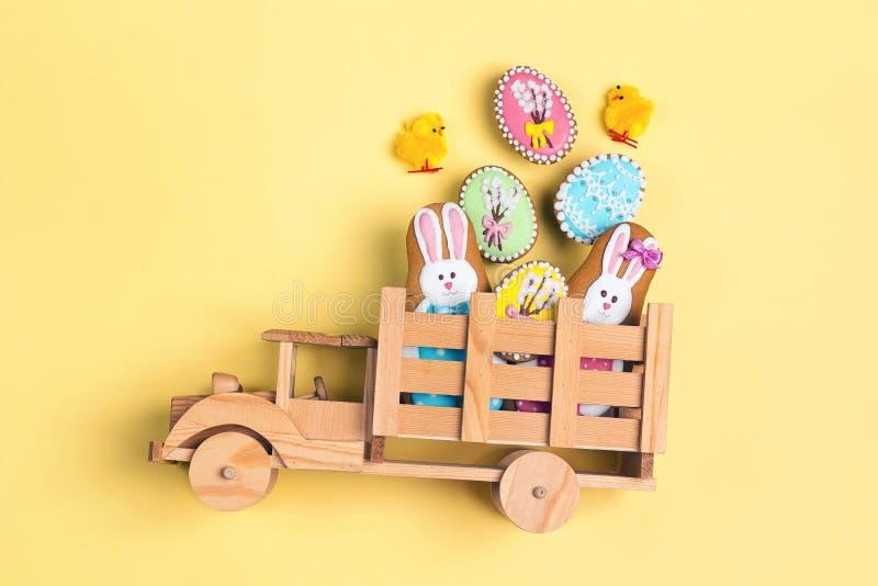 Camion di legno del giocattolo con i biscotti casalinghi del pan di zenzero di Pasqua nella parte posteriore su fondo giallo Deco immagine stock