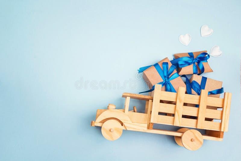 Camion di legno del giocattolo con il contenitore di regalo nella parte posteriore sui wi blu del fondo fotografie stock libere da diritti