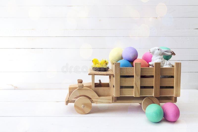 Camion di legno del giocattolo con le uova di Pasqua e un coniglio nella parte posteriore Stazione termale immagine stock libera da diritti