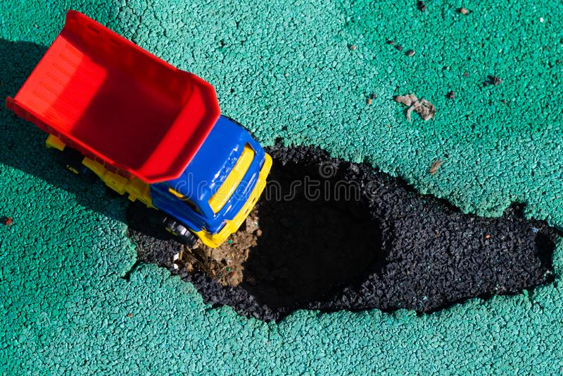 Camion di plastica del giocattolo con un corpo rosso fermato davanti al pozzo L'automobile non può andare Foro su asfalto La str fotografia stock
