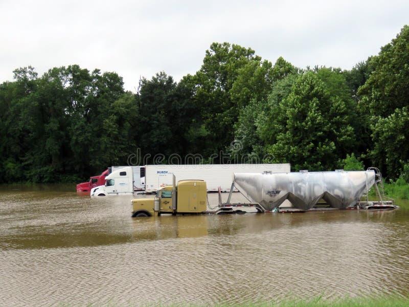 Camion e rimorchi parcheggiati dei semi in acque di inondazione fotografie stock