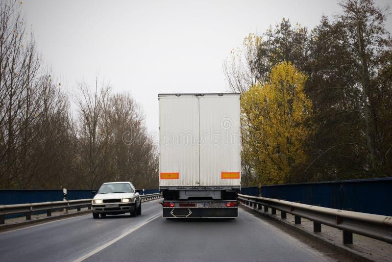Camion ed automobile sulla strada fotografia stock