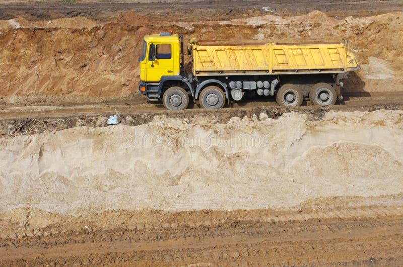 Camion giallo e passare attraverso la terra della ghiaia fotografia stock libera da diritti