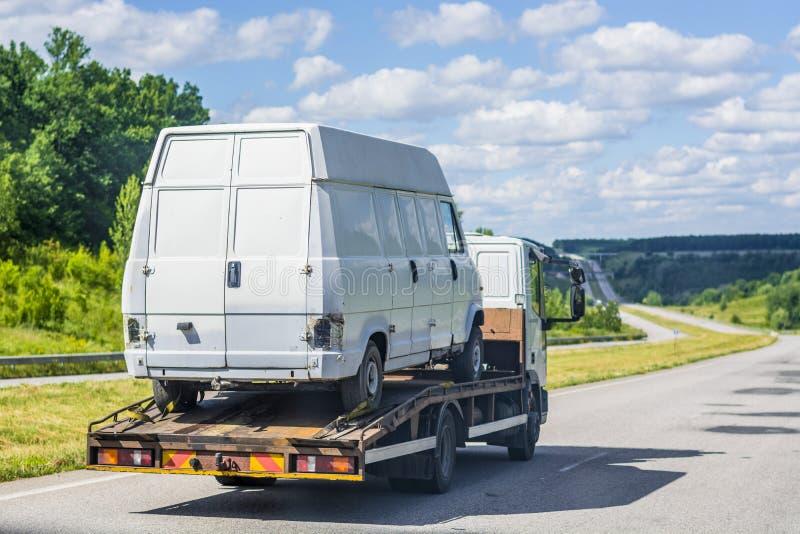 Camion léger - la dépanneuse, transports un blanc, a endommagé, minibus cassé à elle-même le long de la route entre les villes photos libres de droits
