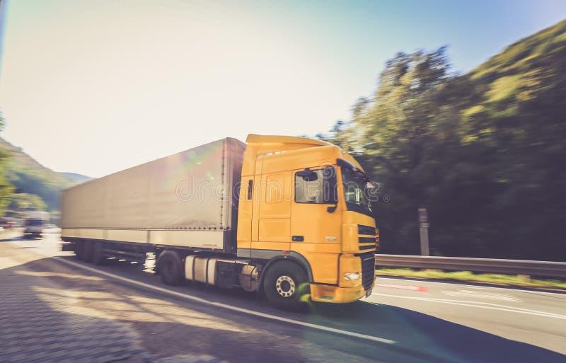 Camion mobile jaune de DAF ajouté à la semi-remorque dans le mouvement situé sur la route photo libre de droits