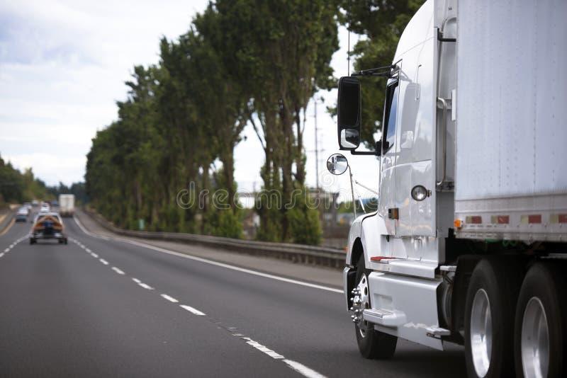 Camion moderno dei semi sull'ampia strada principale che allunga nella distanza fotografia stock