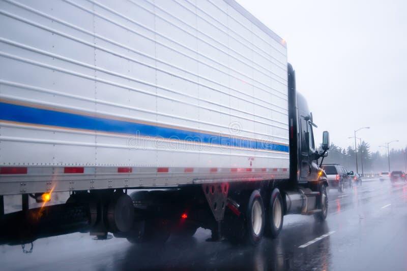 Camion nero dei semi con il rimorchio del guardiamarina sulla pioggia della strada principale immagini stock