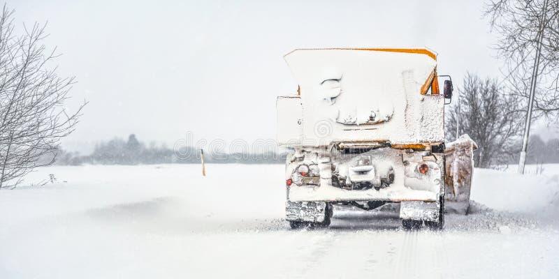 Camion orange de charrue sur la route couverte par neige, le ciel gris et les arbres à l'arrière-plan, vue de dos - entretien des image stock