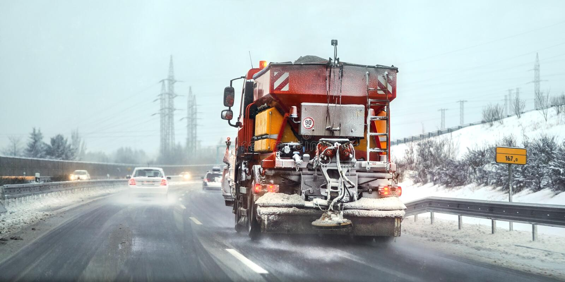 Camion orange de gravillonneuse d'entretien de route répandant le sel de icing sur la route Conditions de conduite dangereuses photos libres de droits