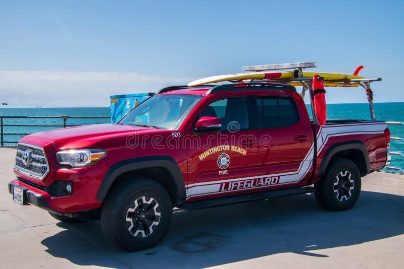 Camion pick-up rouge lumineux de délivrance du feu et de maître nageur de Huntington Beach avec des planches de surf sur le suppo photo libre de droits