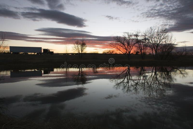 Camion pilotant après coucher du soleil photo stock