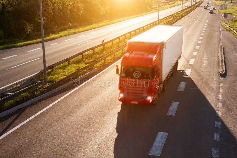 Camion rosso alla luce posteriore sulla strada principale immagine stock