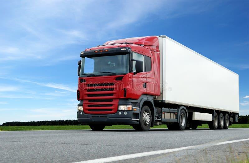 Camion rosso con il rimorchio bianco sopra cielo blu fotografia stock