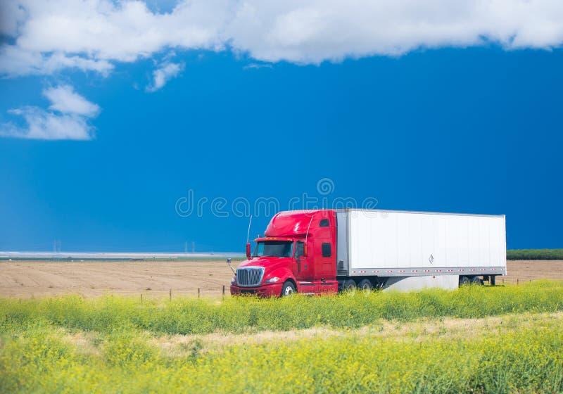 Camion rosso dei semi sulla strada in mezzo al campo immagini stock libere da diritti