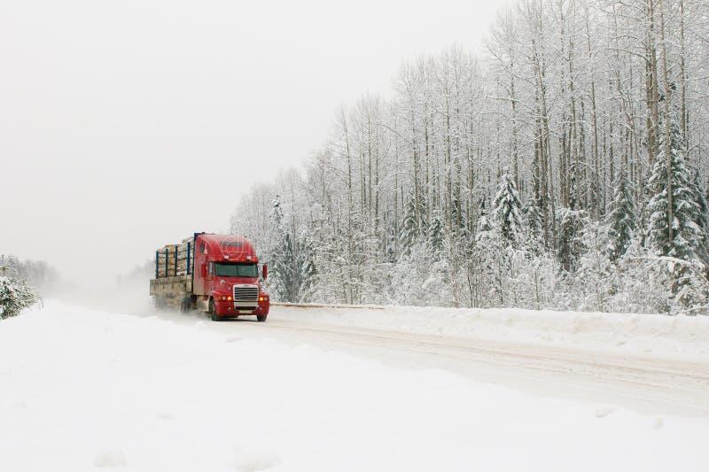 Camion rosso sulla strada di inverno fotografia stock