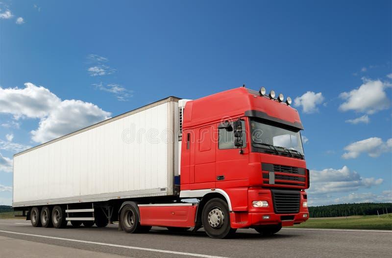 Camion rouge avec la remorque blanche au-dessus du ciel bleu photographie stock libre de droits