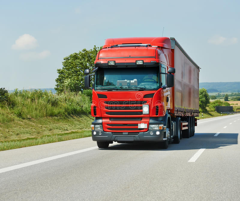 Camion rouge avec la remorque sur la route photographie stock libre de droits