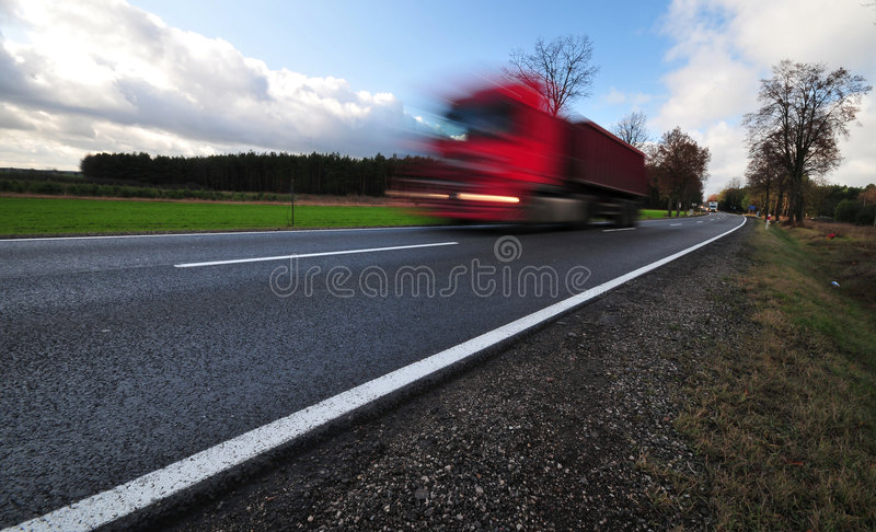Camion rouge dans un mouvement sur la route de macadam photographie stock