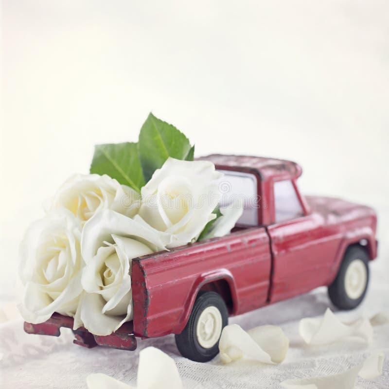 Camion rouge de jouet avec les roses blanches photographie stock libre de droits