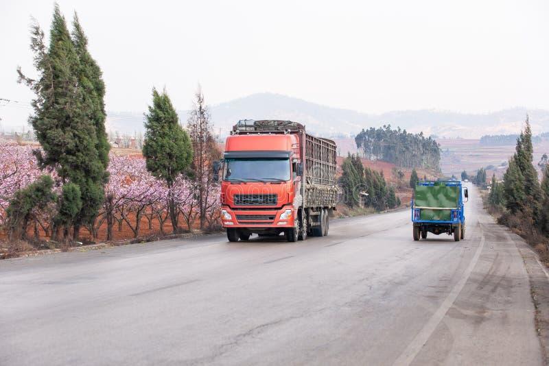 Camion rouge et tracteur conduisant sur la route goudronnée dans le paysage rural de Dongchuan, sud de la Chine Beau bord de la r photos libres de droits