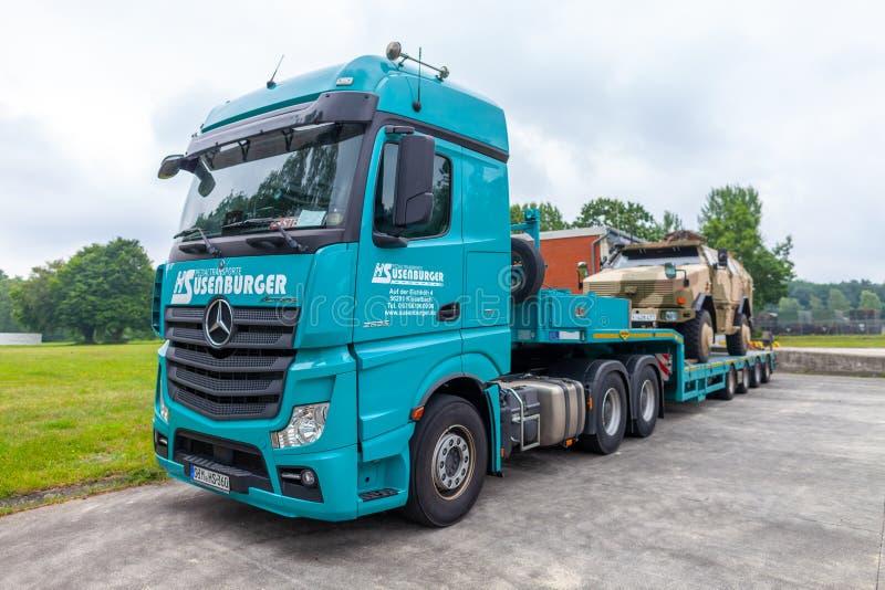 Camion speciale di trasporto da Susenburger con un dingo di KMW sul rimorchio fotografia stock