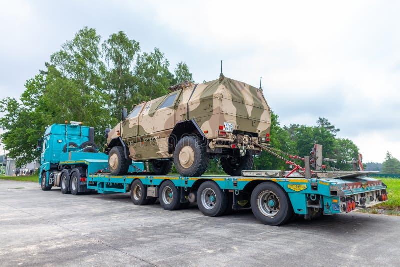 Camion speciale di trasporto da Susenburger con un dingo di KMW sul rimorchio immagini stock libere da diritti