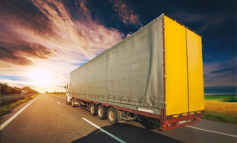 Camion sulla strada che guida lungo la strada asfaltata intorno al giacimento di fioritura giallo del seme di ravizzone in campag fotografia stock