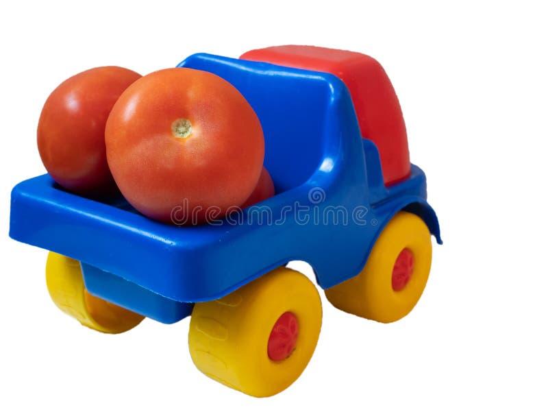 Camion vif coloré de voiture de jouet complètement des tomates rouges photographie stock libre de droits